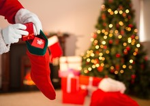 Santa Claus Putting Gifts In Christmas Stocking