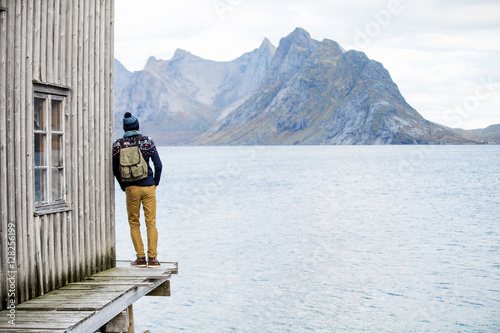 man looking at the mountains, standing on a wooden pier Canvas-taulu