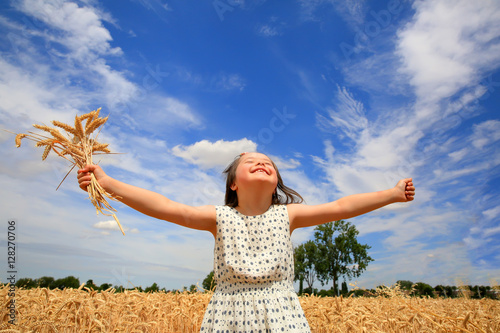 Fotografia  Young girl have fun in the wheat field
