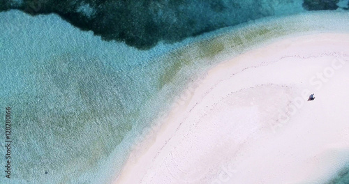 Poster de jardin Vue aerienne Panoramic landscape seascape aerial view over a Maldives Male Atoll island shore. Man standing on the white sandy beach seen from above.