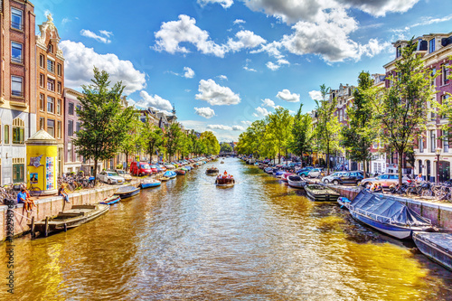 Foto op Plexiglas Amsterdam NETHERLANDS, AMSTERDAM - AUGUST 15, 2011: The view from the bridge over the canal in Amsterdam, cars, bikes and tourists who enjoy. Sunny Day over the canal in Amsterdam, HDR Image.