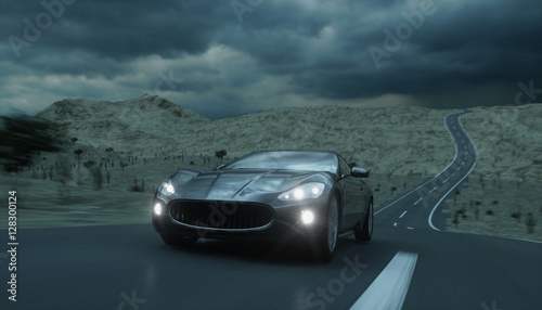 szary-sportowy-samochod-jadacy-wieczorem-droga-przez-pustynie-z-wlaczonymi-swiatlami
