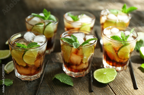 Glasses of cocktail with ice and mint on wooden table closeup Wallpaper Mural