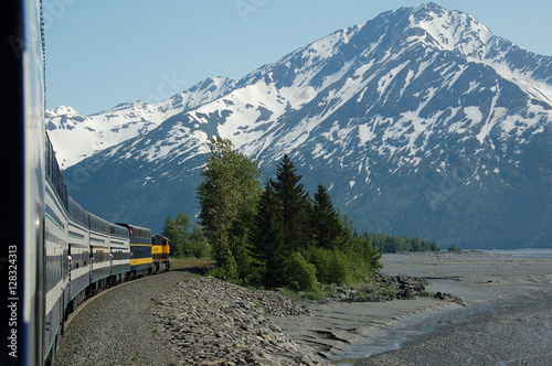 Train rounding bend in front of snowy mountain плакат