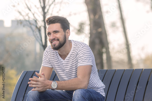 Fototapety, obrazy: Young adult man sitting on a bench, smiling, happy.