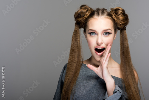 Fotografie, Obraz  Portrait of a beautiful young girl with two ponytails,  open mouth and hand express surprise, shock, gossip