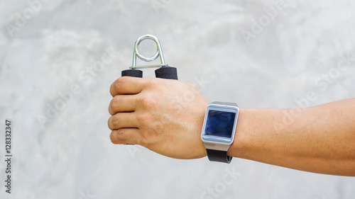 Staande foto Dragen Man wear a smartwatch and use handgrips for exercise.