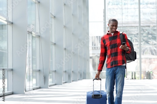 Man walking at airport with suitcase and mobile phone Fototapet