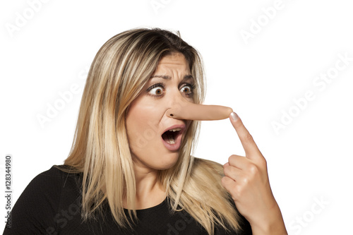Fotografia  shocked young woman touching her elongated nose. concept of lying