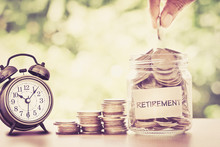 Hand Putting Coins In Glass Jar With Retro Alarm Clock