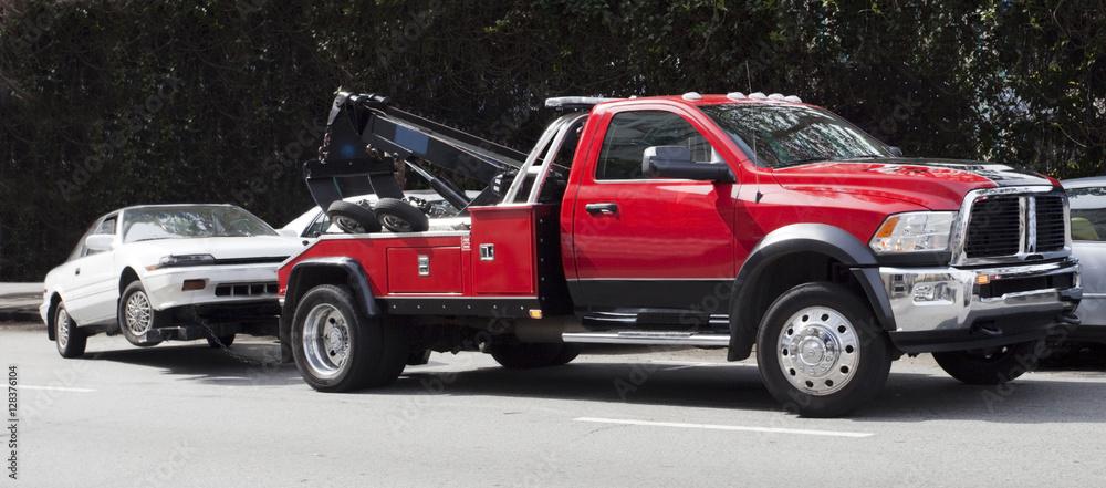 Fototapeta Surprise! Your car is G-O-N-E! Red tow truck hauling away white car. Horizontal.
