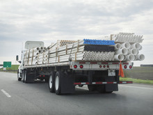 Rear And Side View Of Flatbed Semi Hauling Cargo Of Construction Pipes. Horizontal.