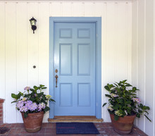 A Front Entrance Of A Home With A Blue Door, Blue Front Door With Flower Pots