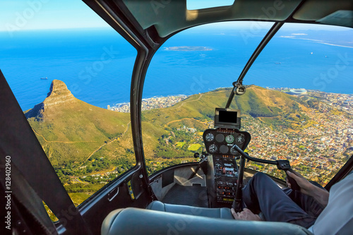 Tuinposter Helicopter Helicopter cockpit flies in Lion's Head, coast and Cape Town in South Africa, with pilot arm and control board inside the cabin.