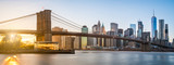 Fototapeta Nowy York - The panorama view of Brooklyn Bridge with Lower Manhattan in the background, lit by sunset