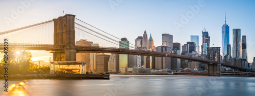 Deurstickers New York The panorama view of Brooklyn Bridge with Lower Manhattan in the background, lit by sunset
