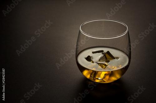 Fotografie, Obraz  glass of whiskey shot against a dark background