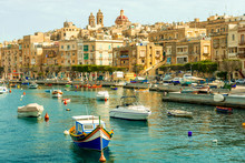 Beautiful Boats In Valletta Harbour With Cityscape On The Background