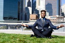 Young African Businessman Meditating Outside At The Lawn