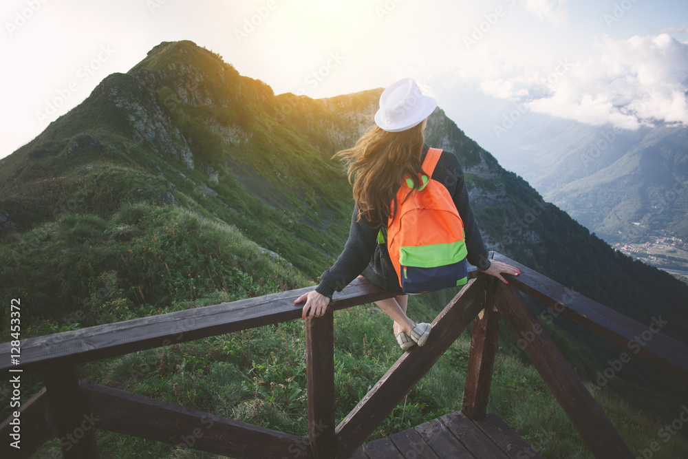 Fototapety, obrazy: Young traveling woman wearing hat and backpack sitting high on the top of the mountain with waving hair, evening with sunset