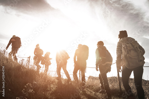 Group of hikers walking on a mountain at sunset