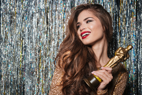 Photo  Smiling woman with long hair holding award and looking away