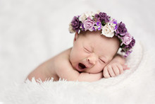 Newborn Sleeping Yawns With Wreath Of Purple Flowers On Light Background, Real Life,  Lifestyle,