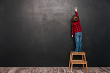 Child Standing On Stool Near Blackboard And Drawing At Board
