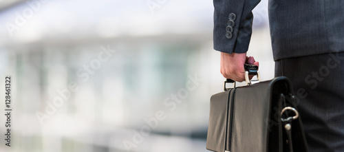 Photo Detail of a businessman holding a leather briefcase