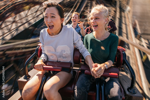 Foto op Plexiglas Amusementspark Happy young people riding a roller coaster