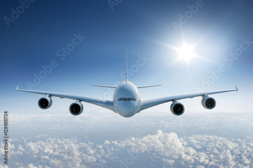 Zdjęcie XXL Duży samolotowy latanie nad chmury w kierunku kamery z słońcem w niebieskim niebie ,.
