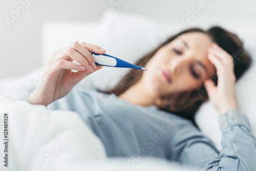 Stampa su Tela  Woman measuring her temperature