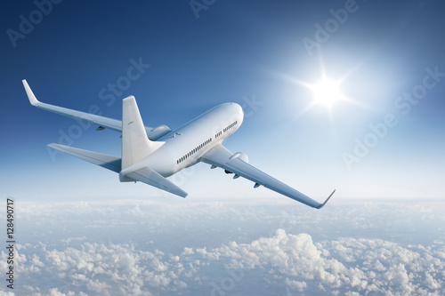 Plagát Airliner flying towards the sun in blue sky