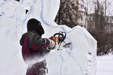 Worker Using Chainsaw Carving An Ice Sculpture