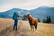 A young man with a backpack met a beautiful horse in the mountai