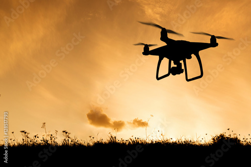 Deurstickers Militair Silhouette of hovering drone taking pictures of nature at sunset