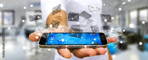 Businessman holding 3D rendering flying email icon over mobile p