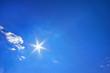 Deep blue sky. Six point sun and clouds