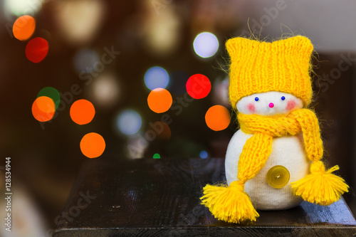 фотография snowman wearing a knitted yellow hat and scarf