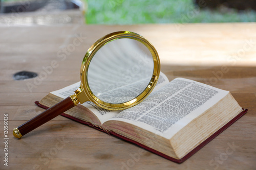 bible book and magnifying glass on wood background Wallpaper Mural