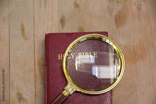 Photo  bible book and magnifying glass on wood background