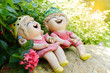Happy boy and girl dolls made from baked clay decorative in a garden