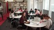 Busy University Library With Students And Tutor