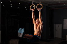Muscular Young Adult On Gymnastics Rings