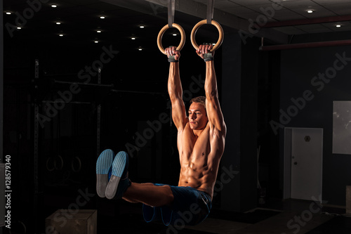 La pose en embrasure Gymnastique Muscular young adult on gymnastics rings