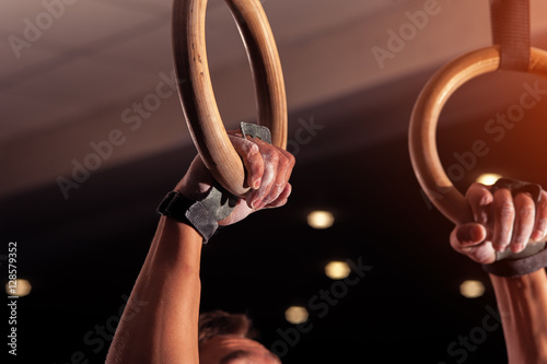 Foto op Canvas Gymnastiek Closeup of male hands with gymnastics rings
