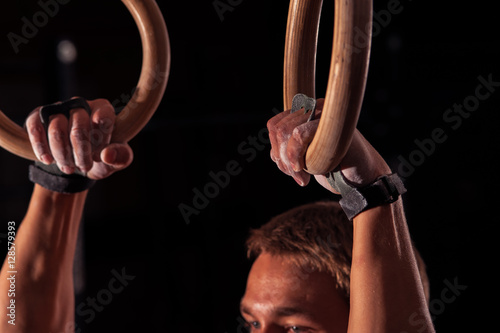 Tuinposter Gymnastiek Male athlete doing exercises with gymnastics rings