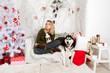 young pretty girl and dog Siberian Husky around the Christmas tr