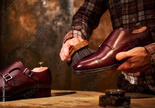 Man polishing leather shoes with brush