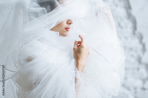 Canvas Print red lips of a beautiful woman with white veil on her face